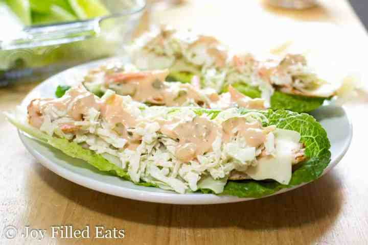 two turkey lettuce wraps with coleslaw and thousand island dressing on a plate