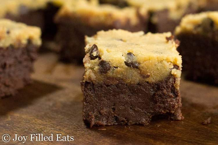 Chocolate Chip Cookie Dough Brownies staggered on a dark wood surface