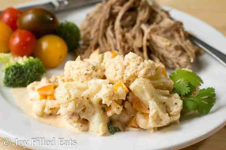 Spicy Cauliflower Potato Salad Recipe on a white plate with pulled pork
