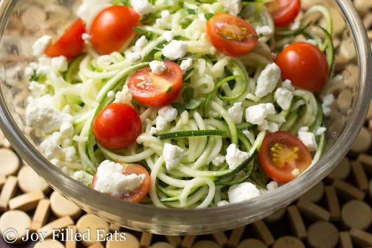 close up of zucchini salad in a glass bowl topped with feta cheese and tomatoes