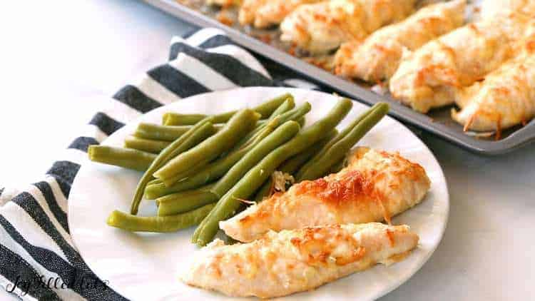 garlic parmesan chicken tenders on a white plate with green beans