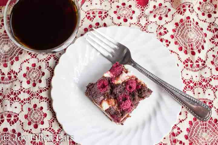 A raspberry brownie on a white plate with a fork and a cup of coffee.