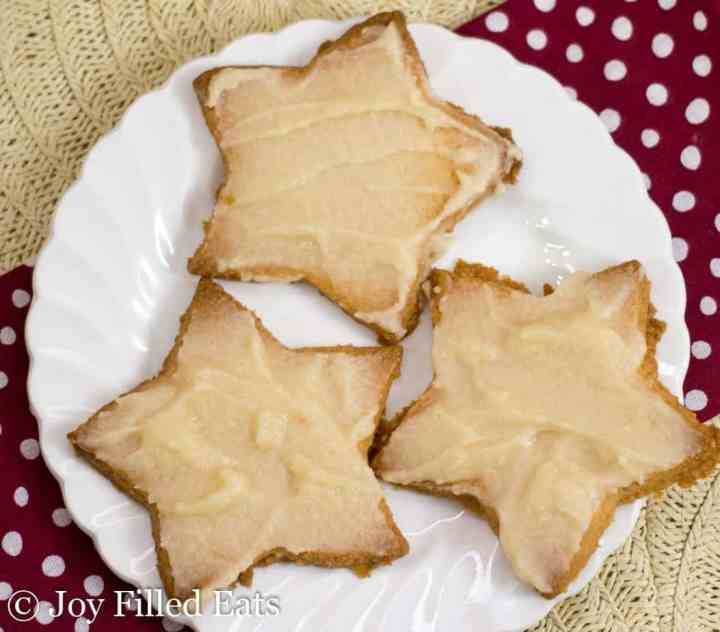 Iced Vanilla Almond Flour Cookies shaped like stars on a small white plate