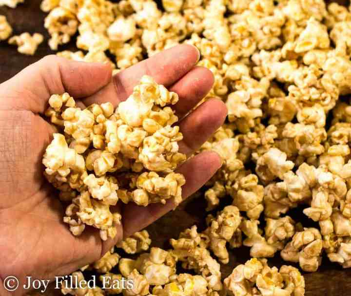 A hand holding salted caramel popcorn.
