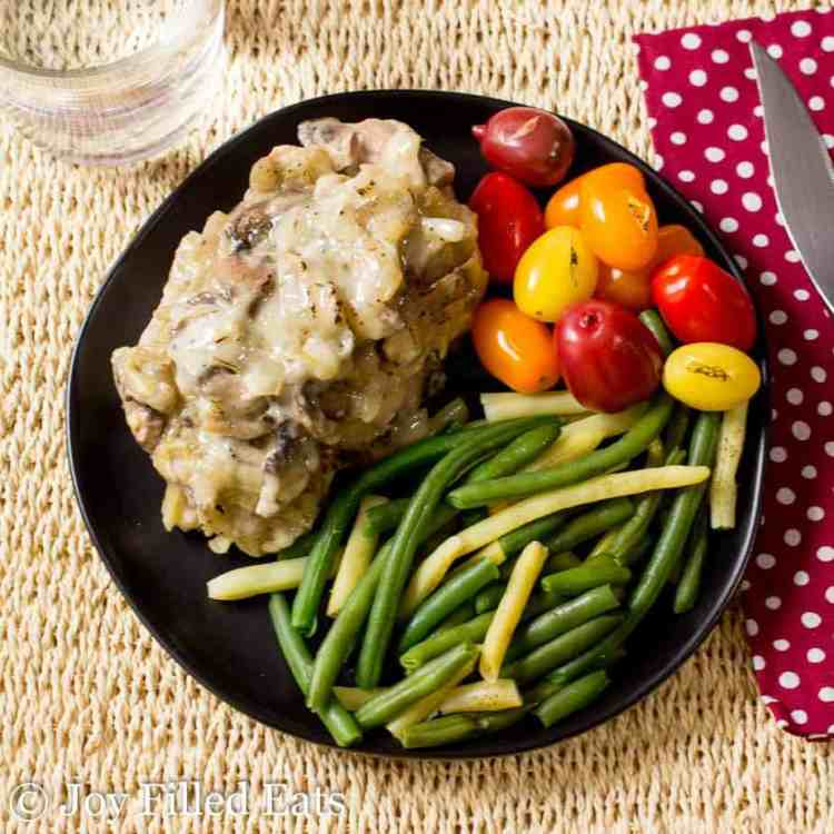 An overhead shot of a black plate with a baked smothered pork chop, green beans, and tomatoes.