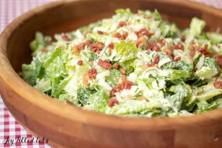 a large wooden salad bowl with keto caesar salad with bacon