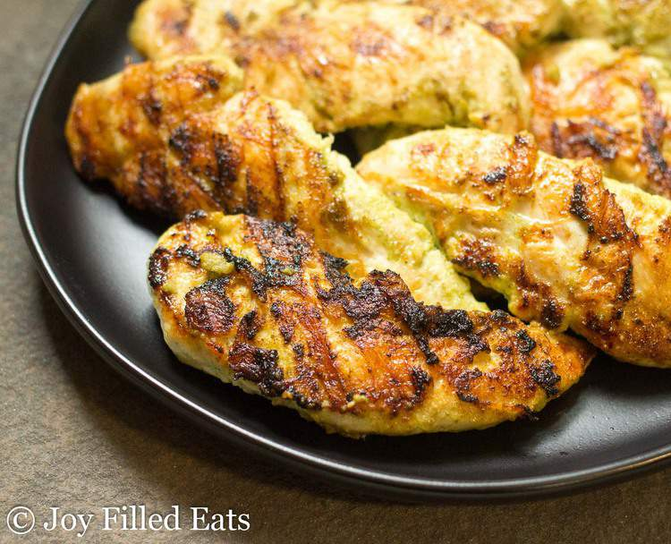 grilled Cilantro Lime Chicken Marinaded chicken tenderloins on a black plate