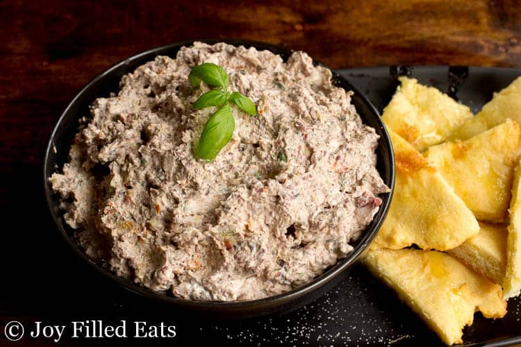 A black bowl of Mediterranean Cheese Spread Recipe with Fathead Pita Dippers