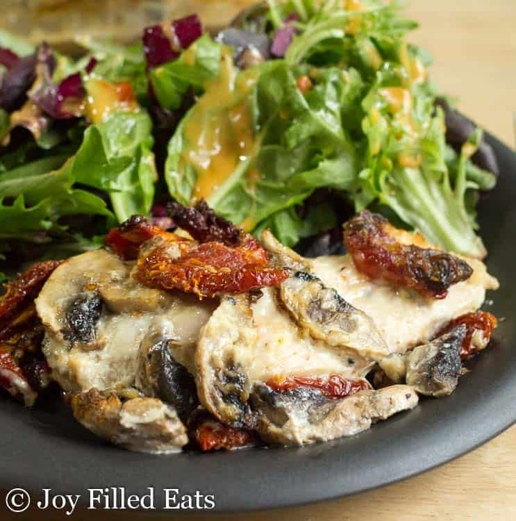 baked chicken breast and salad on a black plate