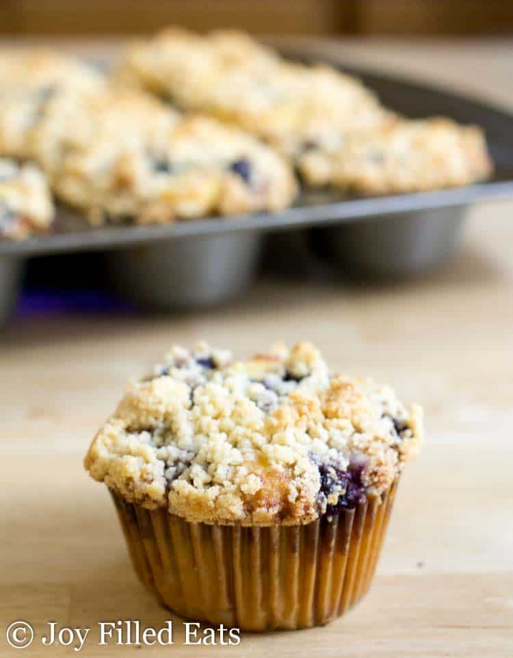 One of the Blueberry Muffins with Crumb Topping on a wood surface with a tray of muffins in the background