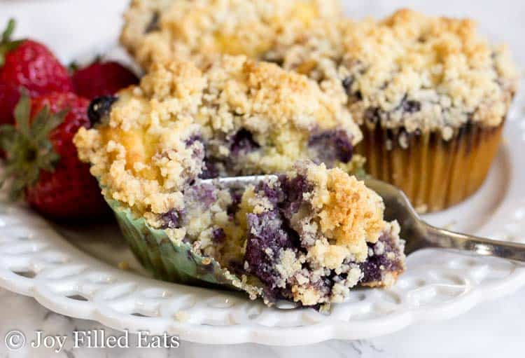 A fork cutting off a bite of one of the a healthy blueberry muffins