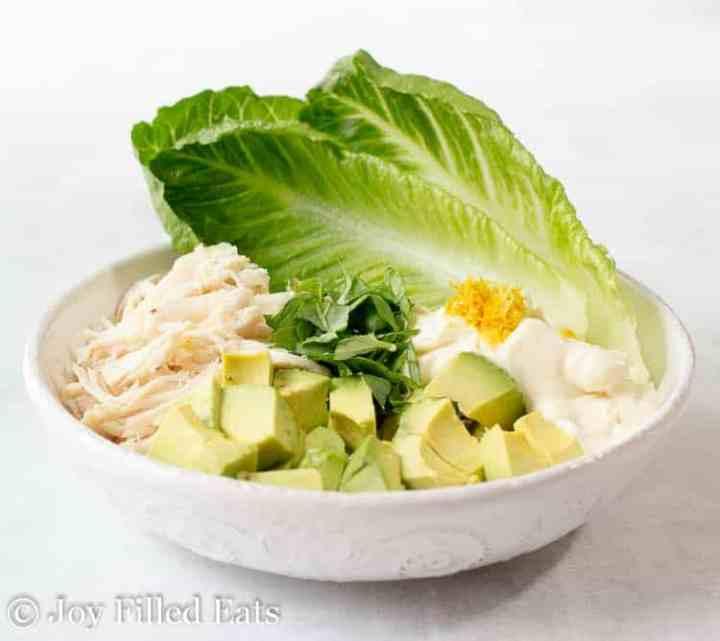 A large bowl with romaine lettuce leaves, shredded chicken, avocado, fresh basil, mayo, and lemon zest.