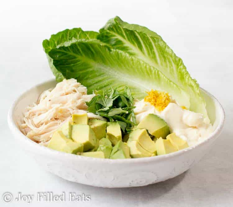 A large bowl with romaine lettuce leaves, shredded chicken, avocado, fresh basil, mayo, and lemon zest.