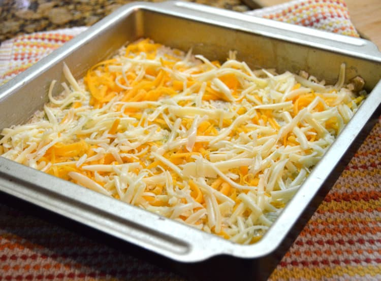 Green Chile Cauliflower Rice topped with shredded cheese in a metal baking dish
