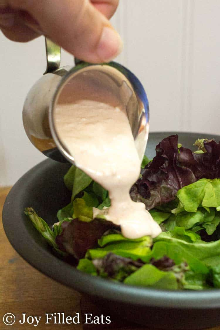 A hand pouring Creamy Garlic Salad Dressing over mixed field greens in a black bowl