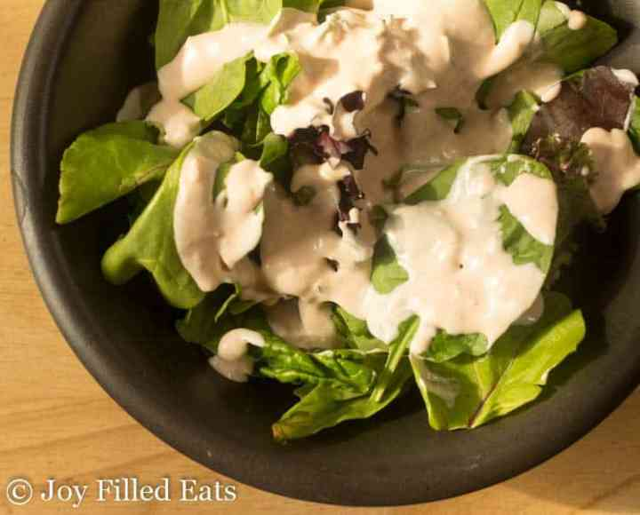 Overhead shot of mixed greens in a black bowl with the Creamy Garlic Salad Dressing Recipe