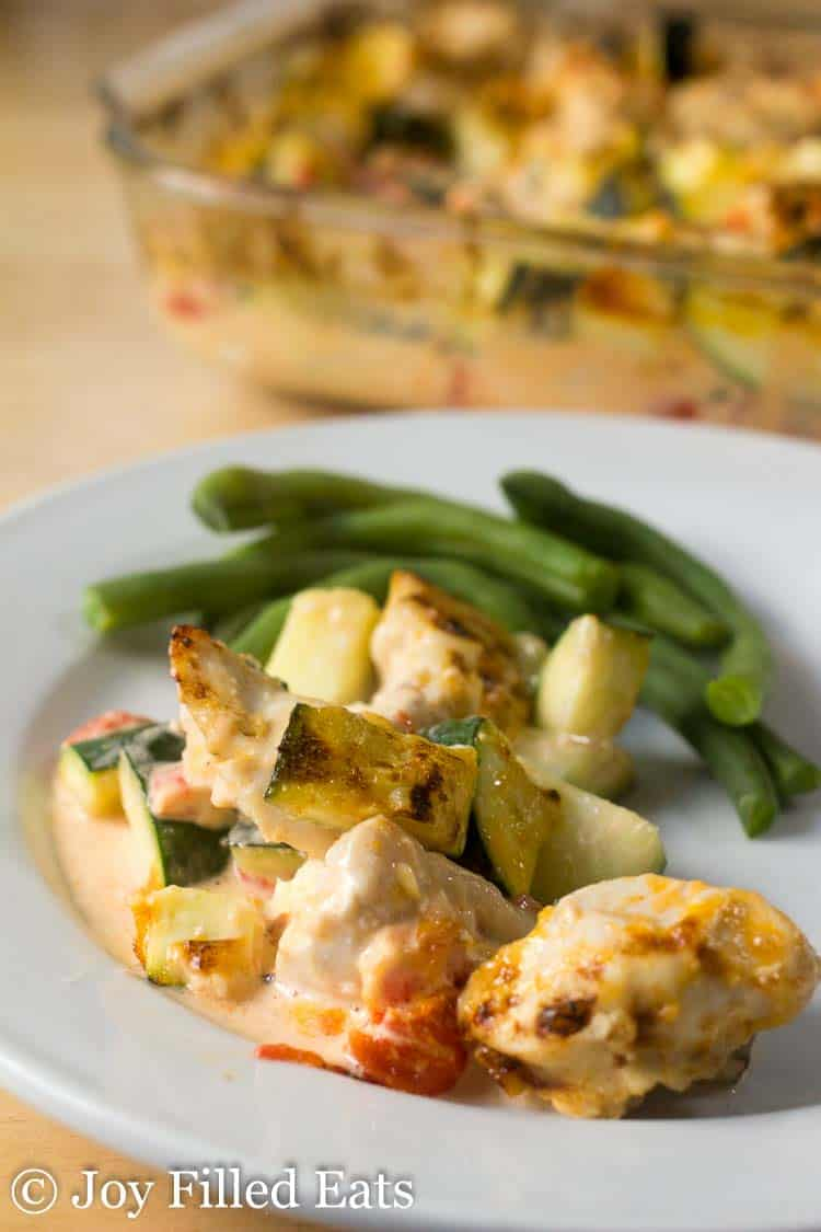 chicken zucchini casserole on a white plate with green beans