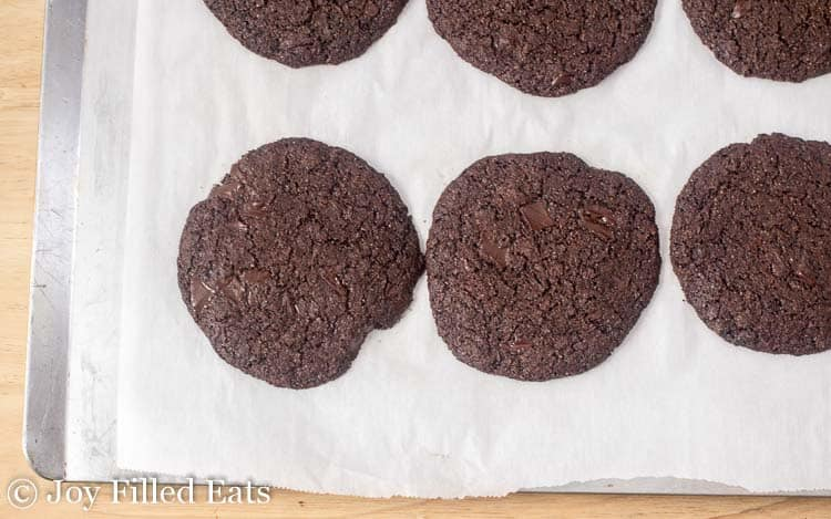 Baked triple chocolate cookies on a metal baking sheet