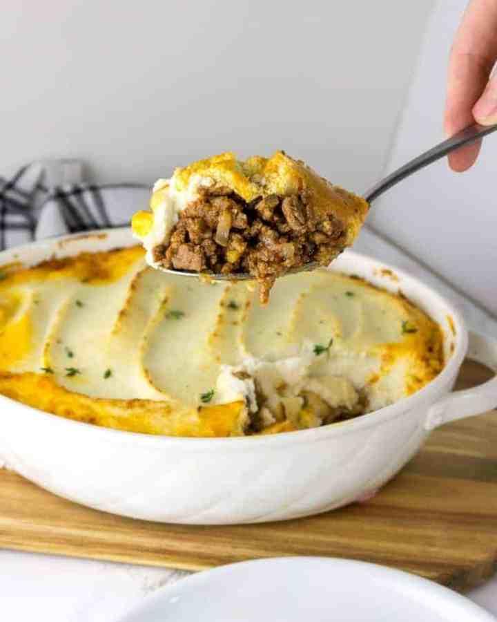 a spoon of shepherd's pie in front of a casserole dish of the shepherd's pie recipe