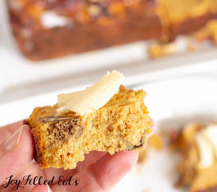 A hand holding a piece of easy pumpkin bread topped with butter