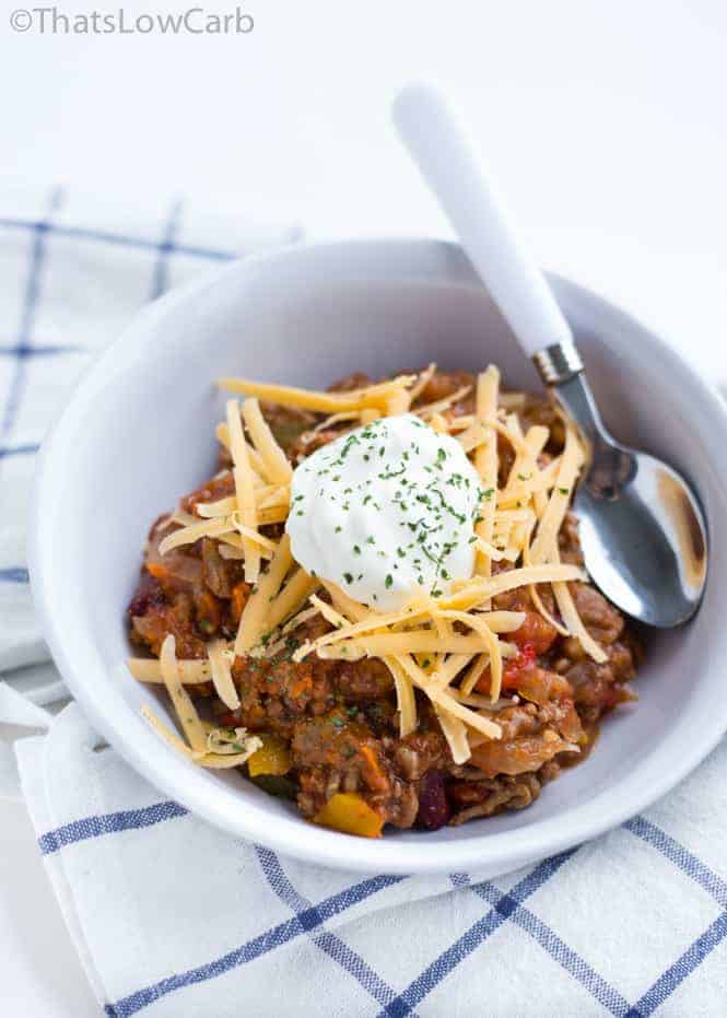 Overhead shot of a bowl of no bean keto chili with cheese and sour cream on top