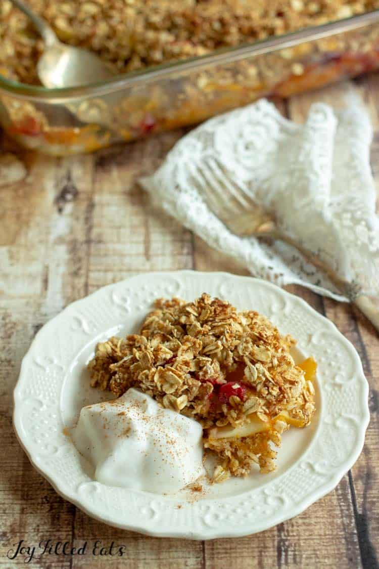 sugar free apple crisp on a plate with a dollop of whipped cream