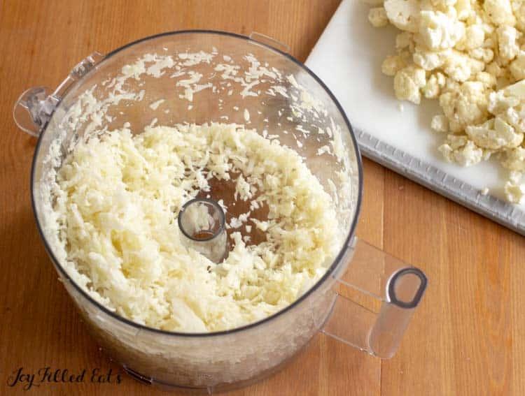 shredded cauliflower in a food processor, florets set aside