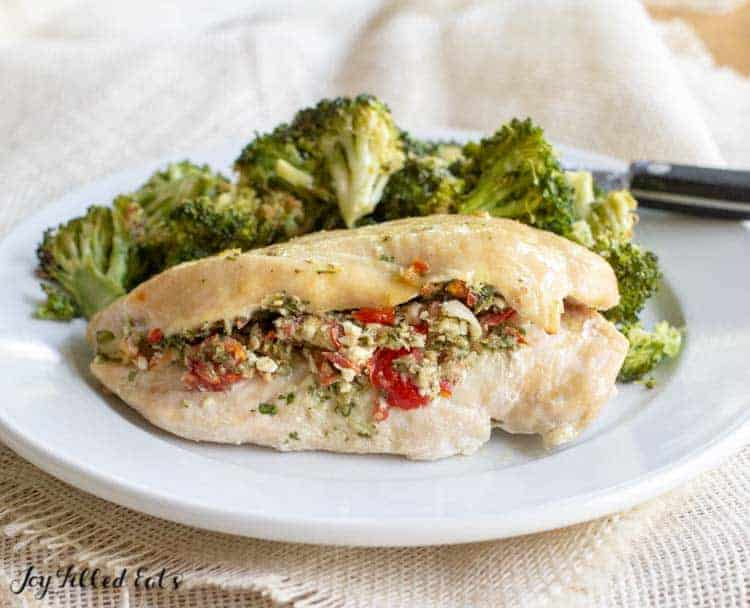 One of the Easy Baked Chicken Breasts Stuffed with Greek Salsa on a white plate with roasted broccoli