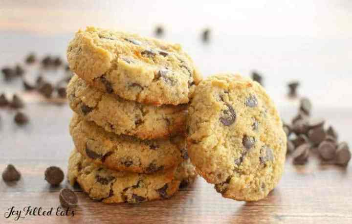 eggless chocolate chip cookies stacked up on a wood backdrop with scattered chocolate chips