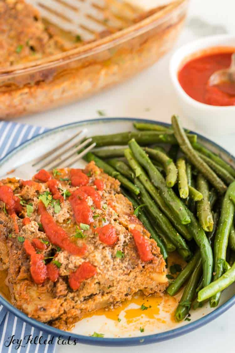 ground turkey meatloaf on a white plate with marinara sauce and vegetables