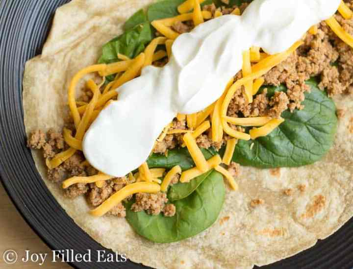 taco meat seasoned with homemade taco seasoning on top of a low carb tortilla with spinach cheese and sour cream
