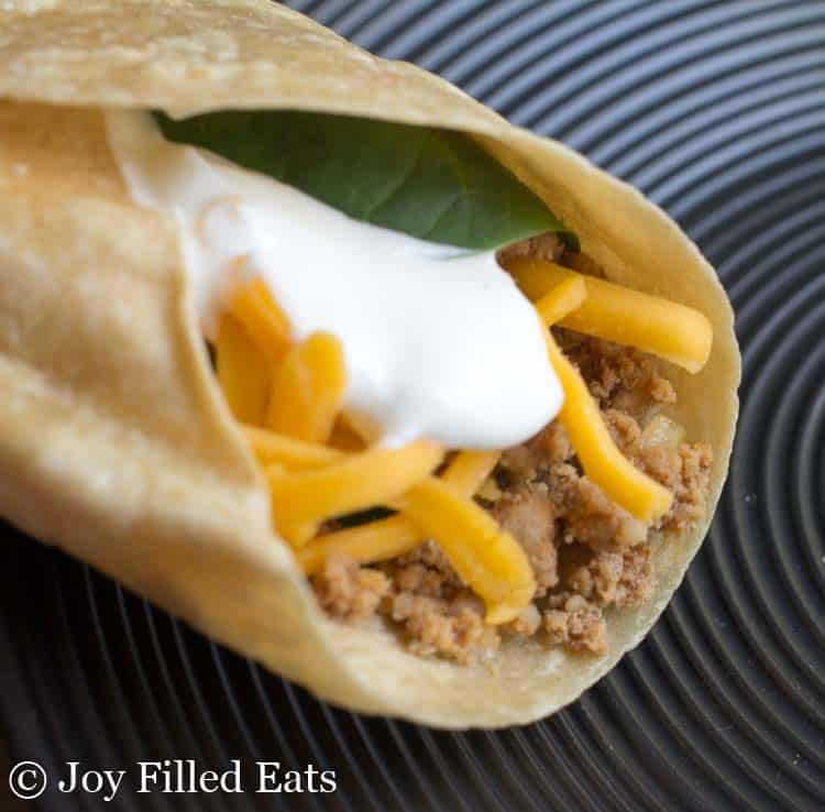 a taco with taco meat on a black plate