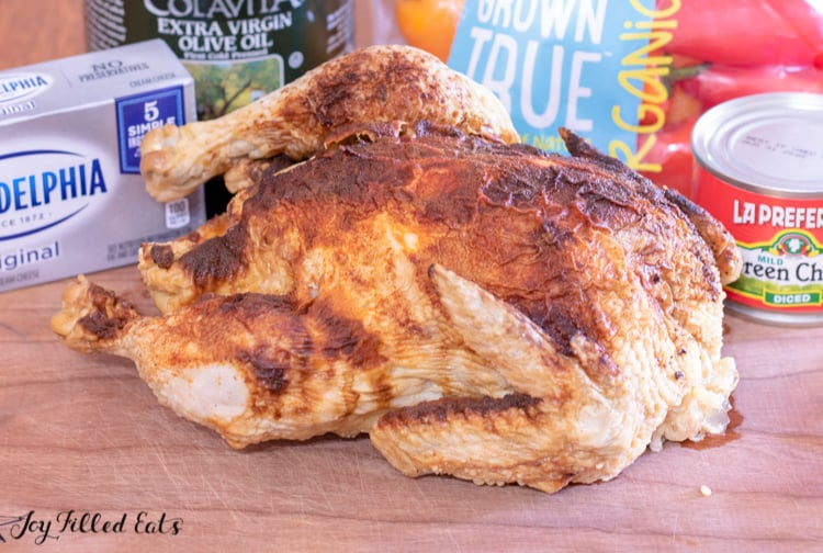 a rotisserie chicken on a cutting board with cream cheese, peppers, green chiles