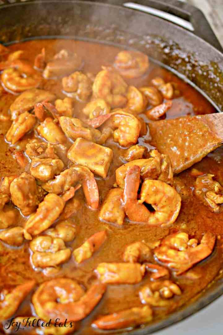a large skillet of indian shrimp curry with chicken