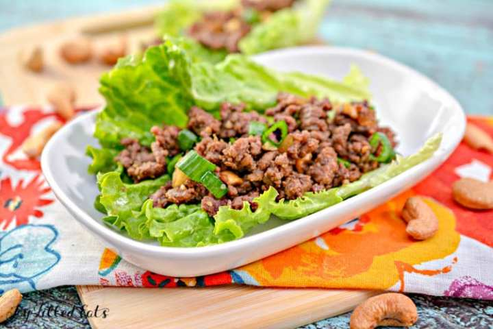 beef lettuce wraps on a white plate with cashews