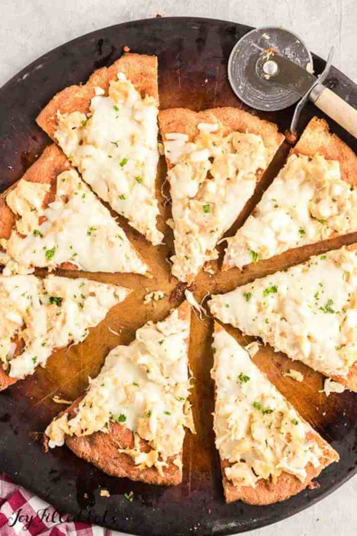 overhead shot of the cut chicken alfredo pizza on the pizza stone