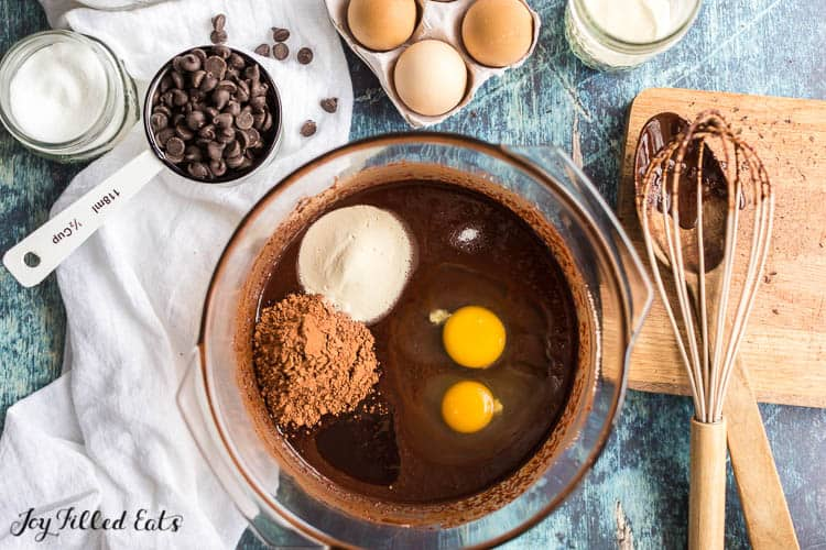 ingredients for the flourless brownies recipe, a glass bowl with melted chocolate, eggs, cocoa, sweetener