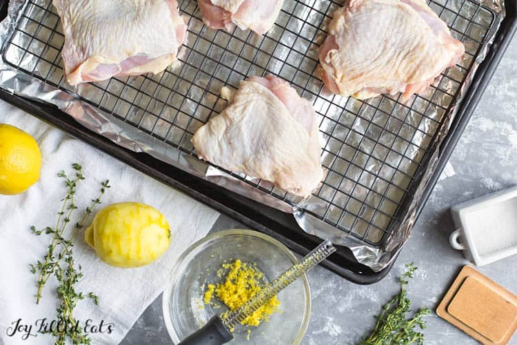 raw chicken thighs on a wire rack with a zested lemon