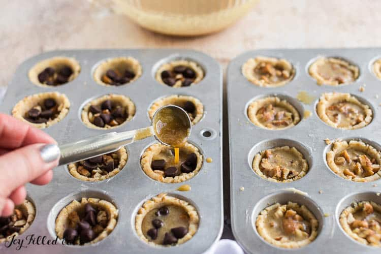 the sweet filling being poured from a teaspoon into the cookie cups
