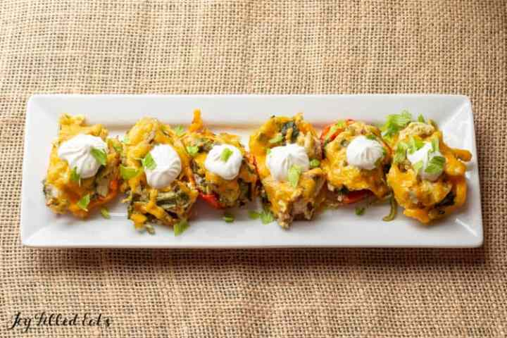 six mini pepper halves topped with chicken, cheese, sour cream, and cilantro