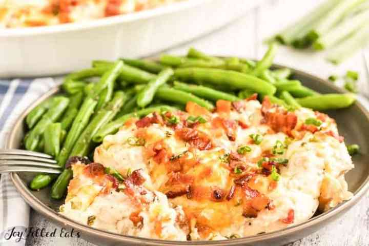 crack chicken on a serving plate with a fork and green beans
