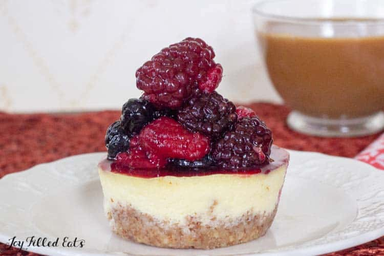 a mini healthy cheesecake on a white plate topped with berries