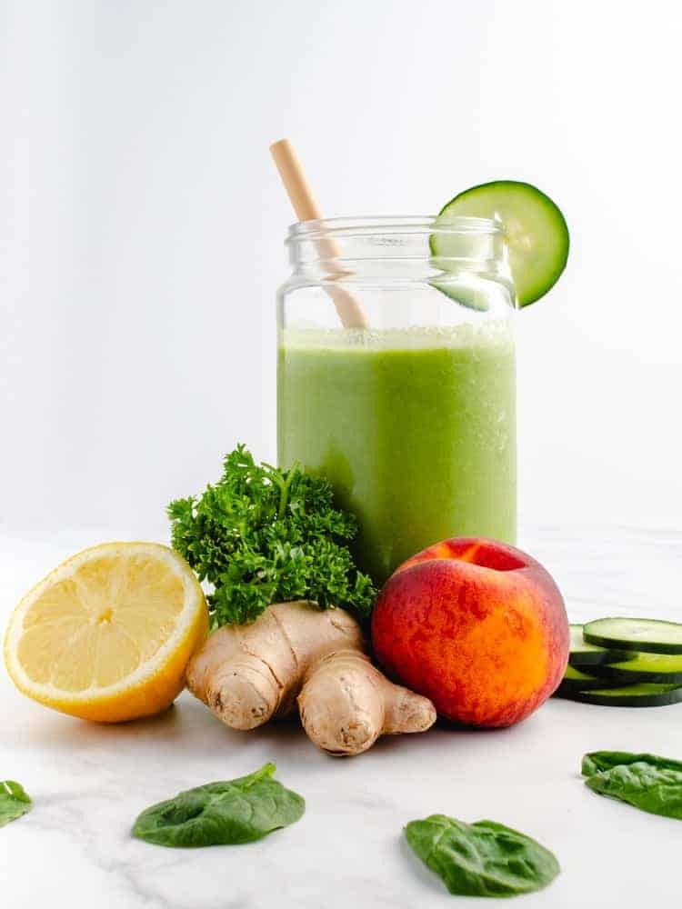 low carb green smoothie in a jar with ingredients around it