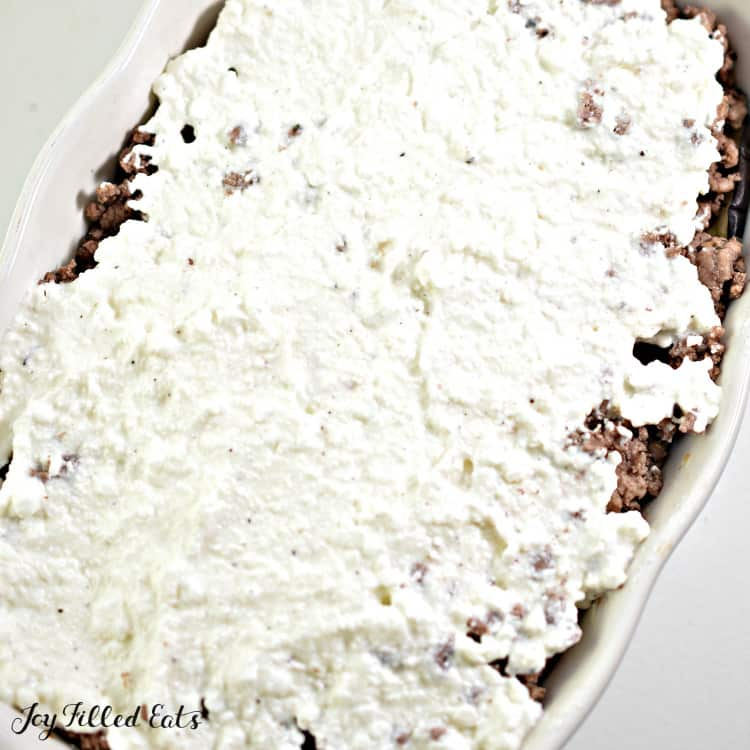 ricotta cheese on top of ground meat in a baking dish