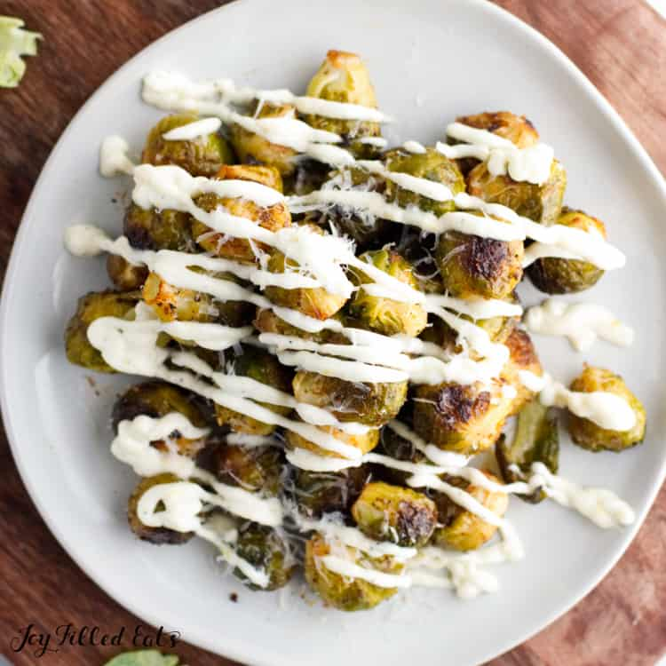 a plate of grilled brussel sprouts topped with aioli