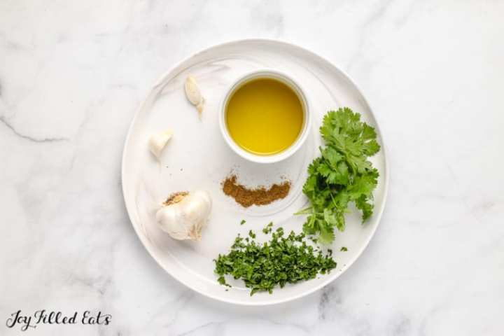 ingredients for chimichurri sauce on a white plate