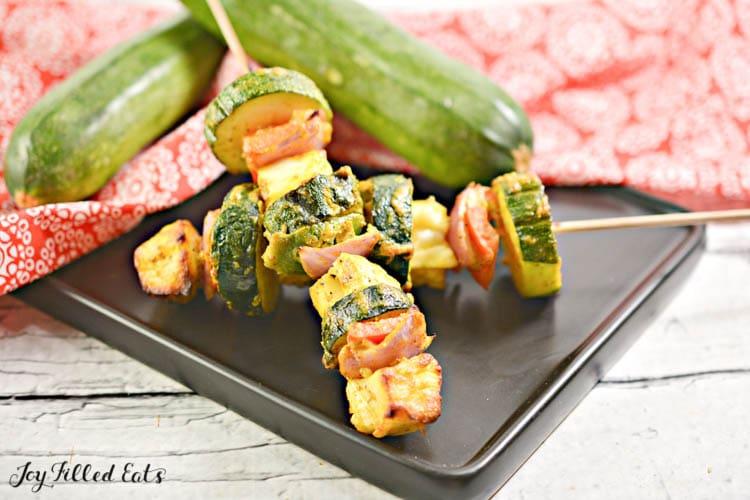 two paneer tikka kebabs on a black plate