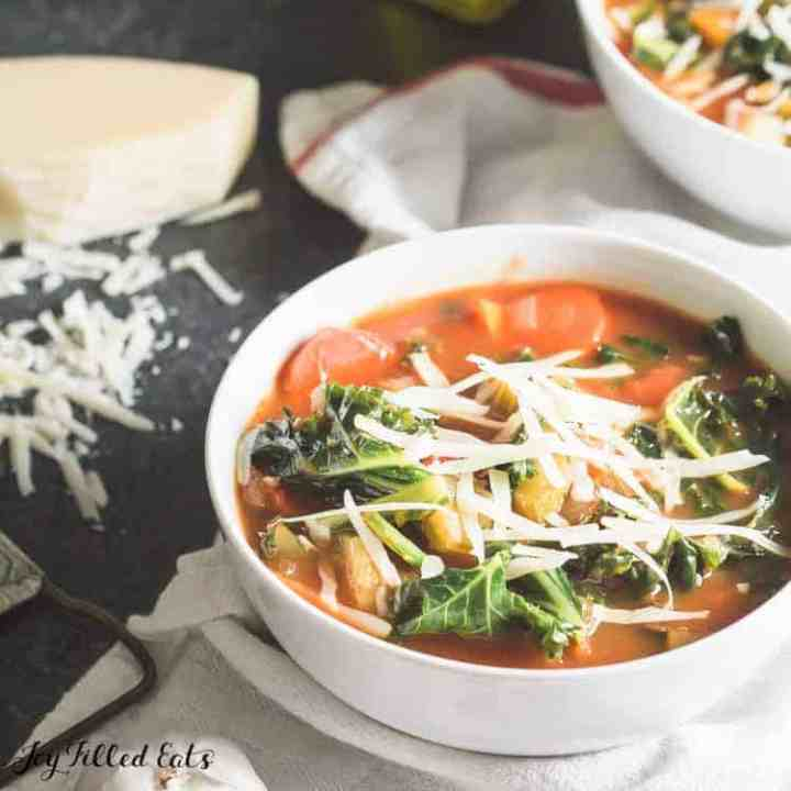 a white bowl of easy vegetable soup with kale