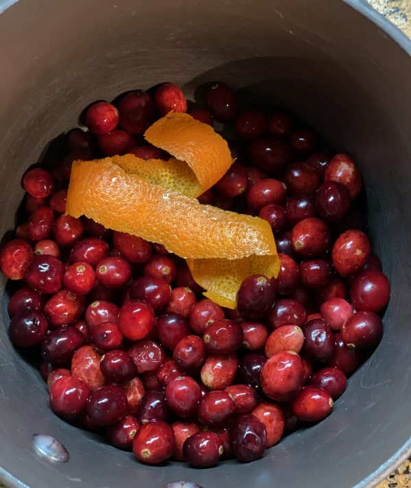 saucepan with cranberries and orange peel