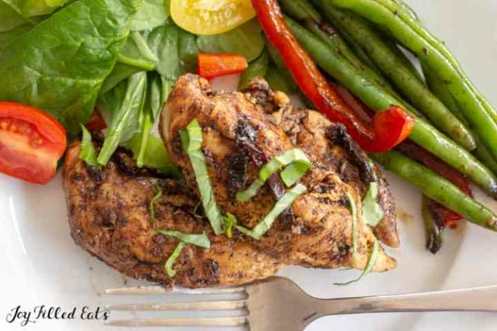 close up of the balsamic chicken on a plate with salad and green beans